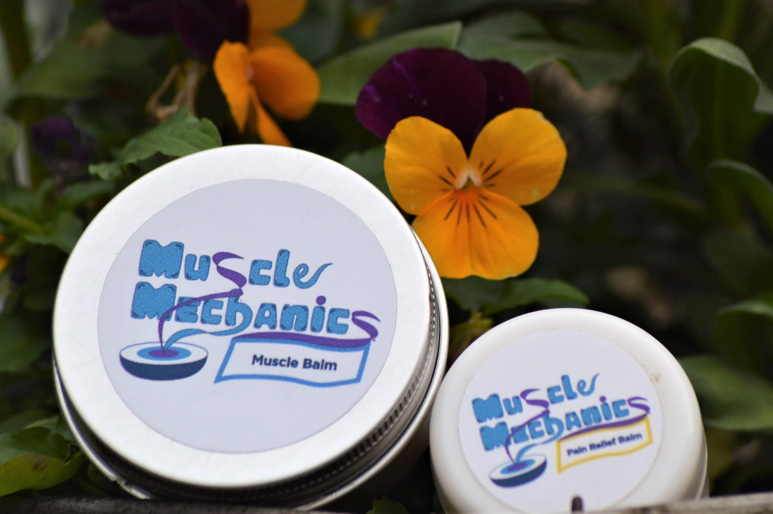Image of Muscle Balm Rub and Pain Relief Balm amongst beautiful yellow flowers
